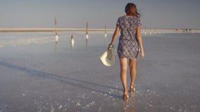 Το λεπτό προκλητικό κορίτσι που απολαμβάνει ένα ηλιοβασίλεμα, περπατά ήπια στο νερό μιας αλατισμένης λίμνης απόθεμα βίντεο