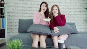 Το λεσβιακό ασιατικό ζεύγος που προσέχει το γέλιο TV και που τρώει popcorn στο καθιστικό στο σπίτι, γλυκό ζεύγος απολαμβάνει την  απόθεμα βίντεο