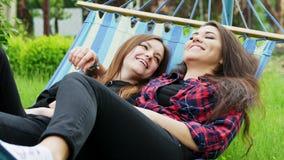 Το λεσβιακό ζεύγος βρίσκεται στην αιώρα στον κήπο Αγκάλιασμα και γέλιο δύο φίλων λεσβιών απόθεμα βίντεο