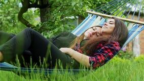 Το λεσβιακό ζεύγος βρίσκεται στην αιώρα στον κήπο Αγκάλιασμα και ύπνος δύο φίλων λεσβιών απόθεμα βίντεο