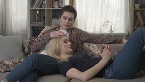 Το λεσβιακό ζεύγος στηρίζεται στον καναπέ, ένα κορίτσι με την κοντή τρίχα ήπια που κτυπά την τρίχα 60 συνεργατών της ` s fps απόθεμα βίντεο