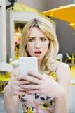 Το λευκό θηλυκό κορίτσι εξετάζει το έξυπνο τηλέφωνό της στο βαθύ κλονισμό υπαίθρια στοκ εικόνα