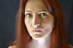 Το λευκό κορίτσι με την κόκκινη τρίχα και τα πράσινα μάτια με τις επεκτάσεις eyelash σε ένα σκοτεινό υπόβαθρο κοιτάζει συναισθημα στοκ εικόνα με δικαίωμα ελεύθερης χρήσης