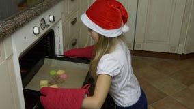 Το λευκό νέο κορίτσι στο κόκκινο καπέλο έρχεται στην κουζίνα και το κοίταγμα στο φούρνο, cookiew εκεί είναι έτοιμο Ο ανοικτός φού απόθεμα βίντεο