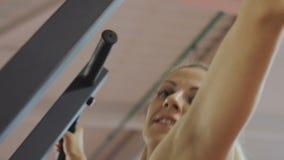 Το λεωφορείο ικανότητας της αθλητικής λέσχης κάνει το τράβηγμα-UPS στον προσομοιωτή για την ενίσχυση των μυών ώμων Μια γυναίκα κά απόθεμα βίντεο