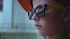 Το λυπημένο αγόρι στα γυαλιά ηλίου στον αερολιμένα, το παιδί βλέπει μακριά, συναντά κάποιο, σπασμένες το s ελπίδες παιδιών ` φιλμ μικρού μήκους