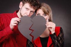 Το λυπημένο ζεύγος κρατά τη σπασμένη καρδιά στοκ εικόνα