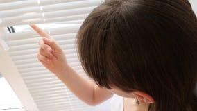 Το λυπημένο κορίτσι κοιτάζει μέσω του παραθύρου μέσω των τυφλών και χαμογελά φιλμ μικρού μήκους