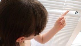 Το λυπημένο κορίτσι κοιτάζει μέσω του παραθύρου μέσω των τυφλών φιλμ μικρού μήκους