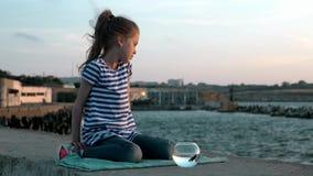 Το λυπημένο κορίτσι παιδιών κάθισε στην ακτή με τα ψάρια του ένα στρογγυλευμένο καλοκαίρι ενυδρείων υπαίθρια περιβάλλον έννοιας φιλμ μικρού μήκους