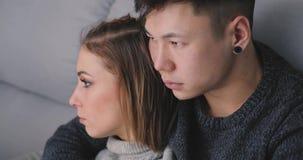 Το λυπημένο νέο ζεύγος κάθεται μαζί στον καναπέ και το αγκάλιασμα απόθεμα βίντεο