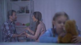 Το μάταιο αγκάλιασμα κοριτσιών teddybear τη βροχερή ημέρα, ακούοντας γονείς μαλώνει, πρόβλημα φιλμ μικρού μήκους