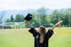 Το μέλλον αγκαλιάσματος κοριτσιών απόφοιτων φοιτητών και ανατρέχει στον ουρανό, φορά GR στοκ φωτογραφία με δικαίωμα ελεύθερης χρήσης