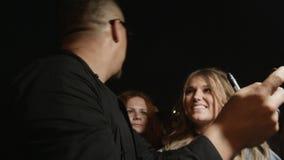 Το μέλος συμμορίας κινηματογραφήσεων σε πρώτο πλάνο παίρνει τη φωτογραφία με τους νέους ανεμιστήρες μετά από τη συναυλία φιλμ μικρού μήκους