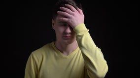 Το μέσης ηλικίας καυκάσιο άτομο στο κίτρινο πουλόβερ που facepalm υπογράφει για να παρουσιάσει ενόχληση στη κάμερα στο μαύρο υπόβ απόθεμα βίντεο