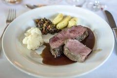 Το μέσο έψησε την μπριζόλα και τις πατάτες βόειου κρέατος στο πιάτο στο άσπρο υπόβαθρο, τοπ άποψη στη σχάρα Στοκ Εικόνα