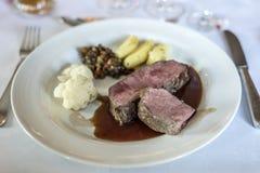 Το μέσο έψησε την μπριζόλα και τις πατάτες βόειου κρέατος στο πιάτο στο άσπρο υπόβαθρο, τοπ άποψη στη σχάρα Στοκ εικόνες με δικαίωμα ελεύθερης χρήσης