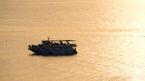 Το μέσο επιβατηγό πλοίο κρουαζιέρας που πλέει με τη θάλασσα στο ηλιοβασίλεμα Σκιαγραφίες των ανθρώπων στο σκάφος φιλμ μικρού μήκους