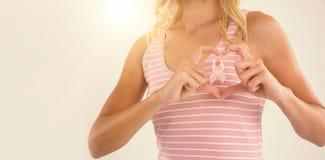 Το μέσο τμήμα της νέας γυναίκας που κάνει τη μορφή καρδιών με παραδίδει την κορδέλλα Στοκ Εικόνα