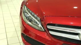 Το μέτωπο του νέου κόκκινου αυτοκινήτου Προβολέας της νέας μηχανής Άποψη του νέου αυτοκινήτου σειρών στη νέα αίθουσα εκθέσεως αυτ απόθεμα βίντεο