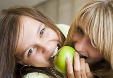 το μήλο τρώει τα κορίτσια σε δύο θέλει Στοκ Εικόνες