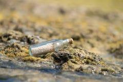 Το μήνυμα σε ένα μπουκάλι έπλυνε στην ξηρά στην τροπική παραλία Στοκ Φωτογραφία