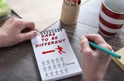Τολμήστε να είστε διαφορετική έννοια σε ένα σημειωματάριο στοκ φωτογραφία