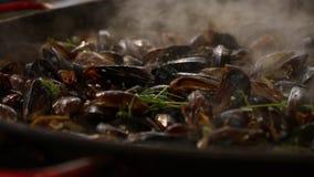 Το μαγείρεμα έβρασε τα ψημένα μύδια στον ατμό στο μεγάλο τηγανίζοντας τηγάνι φιλμ μικρού μήκους
