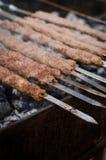 Το μαγείρεμα ατόμων που μαρινάρεται shashlik ή shish kebab, το κρέας ψήνοντας στη σχάρα στο οβελίδιο μετάλλων, κλείνει επάνω Εκλε Στοκ Φωτογραφίες