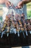 Το μαγείρεμα ατόμων που μαρινάρεται shashlik ή shish kebab, το κρέας ψήνοντας στη σχάρα στο οβελίδιο μετάλλων, κλείνει επάνω Εκλε Στοκ φωτογραφία με δικαίωμα ελεύθερης χρήσης