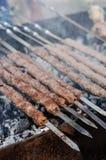 Το μαγείρεμα ατόμων που μαρινάρεται shashlik ή shish kebab, το κρέας ψήνοντας στη σχάρα στο οβελίδιο μετάλλων, κλείνει επάνω Εκλε Στοκ Εικόνες