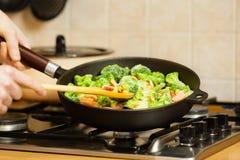 Το μαγείρεμα γυναικών ανακατώνει παγωμένο το τηγανητά λαχανικό στο τηγάνι στοκ φωτογραφία με δικαίωμα ελεύθερης χρήσης