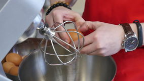 Το μαγείρεμα, κτυπώντας αυγά με ηλεκτρικό χτυπά ελαφρά στο κύπελλο θηλυκή μίξη χεριών αυγών κύπελλων απόθεμα βίντεο