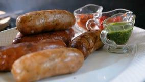 Το μαγείρεμα στα λουκάνικα σχαρών βρίσκεται σε ένα πιάτο κοντά σε διάφορες σάλτσες Πιάτα κρέατος από μια σχάρα απόθεμα βίντεο