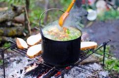 Το μαγείρεμα της σούπας στην πυρκαγιά Στοκ Εικόνες