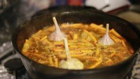 Το μαγείρεμα pilaf, shef προσθέτει το σκόρδο και τα πράσινα πιπέρια τσίλι σε μια κατσαρόλα χυτοσιδήρων απόθεμα βίντεο