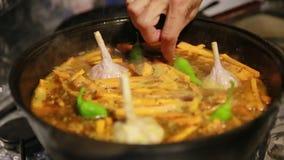 Το μαγείρεμα pilaf, shef προσθέτει το σκόρδο και τα πράσινα πιπέρια τσίλι σε μια κατσαρόλα χυτοσιδήρων φιλμ μικρού μήκους
