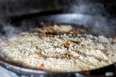 Το μαγειρεύοντας ρύζι για το pilaw ή το paella στο καζάνι σιδήρου ανοίγει πυρ Καπνός και ατμός Νόστιμα τρόφιμα που προετοιμάζουν  στοκ φωτογραφίες