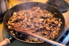 Το μαγειρεύοντας Champignons μανιτάρι με το ξύλινο βατραχοπέδιλο ανακατώνει στο τηγάνι στοκ εικόνες