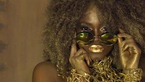 Το μαγικό υπερφυσικό χρυσό θηλυκό πρότυπο αφροαμερικάνων στα ογκώδη γυαλιά ηλίου με φωτεινό ακτινοβολεί makeup, στιλπνός χρυσός απόθεμα βίντεο