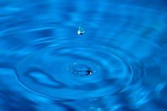 Το μακρο κυριώτερο σταγονίδιο σπάζει την επιφάνεια του νερού Στοκ Φωτογραφία