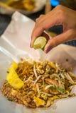 Το μαξιλάρι Ταϊλανδός, ανακατώνει τα νουντλς τηγανητών με τις γαρίδες και συμπιέζει ένα λεμόνι Στοκ εικόνες με δικαίωμα ελεύθερης χρήσης