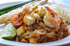 Το μαξιλάρι Ταϊλανδός ανακατώνει το τηγανισμένο νουντλς ρυζιού με τη γαρίδα και το αυγό στο πιάτο Στοκ Εικόνες