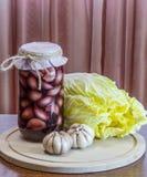 Το μαριναρισμένο σκόρδο στο α μπορεί και κινεζικό λάχανο Στοκ Εικόνες