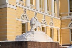 Το μαρμάρινο λιοντάρι κρατά ψηλά τον πυρήνα ποδιών, κοντά στην είσοδο του παλατιού Mikhailovsky κρατικών ρωσικού μουσείων, Άγιος  στοκ εικόνες