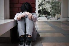 Το ματαιωμένο εξαντλημένο νέο ασιατικό επιχειρησιακό άτομο κάθεται και αγκαλιάζει τα γόνατά του μέχρι την έννοια θωρακικών άνεργη Στοκ Εικόνα