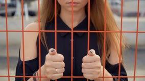 Το ματαιωμένο κορίτσι έβαλε τα χέρια της στο πλέγμα, περίφραξη φιλμ μικρού μήκους