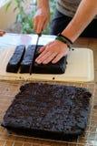 Το μαχαίρι χρήσης αρχιμαγείρων τεμαχίζει το φρέσκο χορτοφάγο κέικ Brownies Στοκ Φωτογραφίες