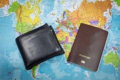 Το μαύρα πορτοφόλι και το διαβατήριο στον κόσμο χαρτογραφούν το υπόβαθρο για το ταξίδι σε όλο τον κόσμο Στοκ φωτογραφία με δικαίωμα ελεύθερης χρήσης