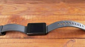 Το μαύρο έξυπνο ρολόι βρίσκεται σε έναν ξύλινο πίνακα Οι πίνακες είναι ορατοί Κινούμενη φωτογραφική μηχανή απόθεμα βίντεο
